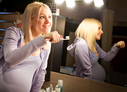 Pregnant woman cleaning her teeth