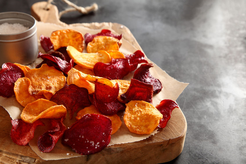 46001784 - crisp crunchy organic vegetable chips with fried or oven-baked potato and beetroot chips served as a finger food snack on a wooden chopping board with sea salt and copyspace