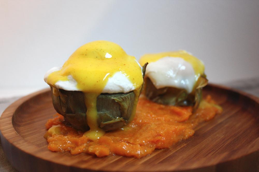 Huevos Benedict sobre alcachofas con puré de calabaza asada y salsa holandesa