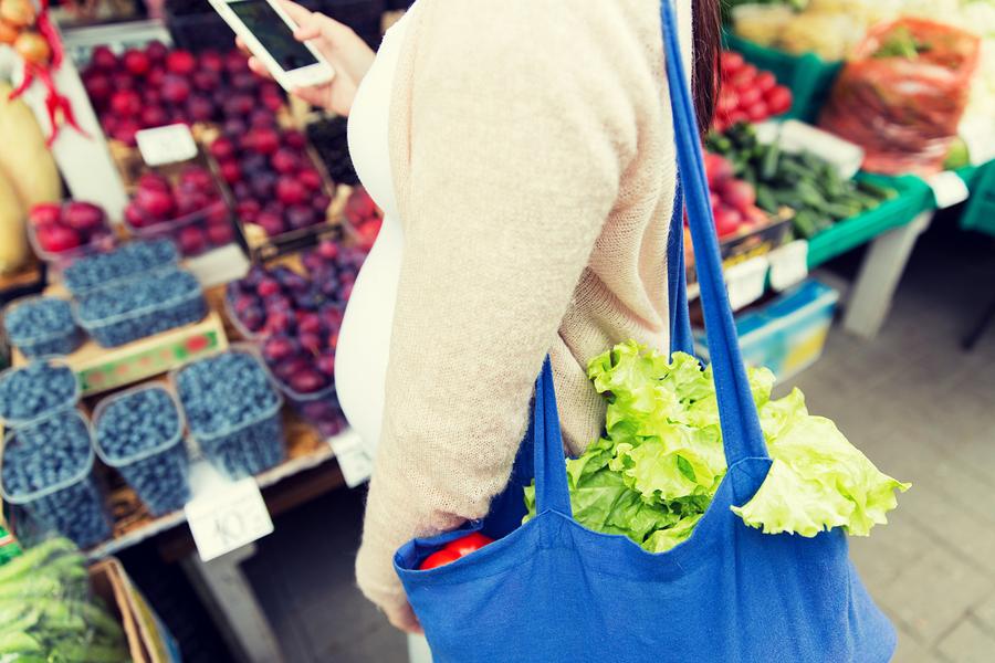 Mujer embarazada comprando en el mercado