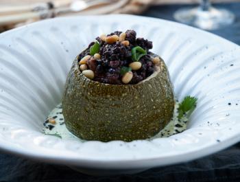 Calabacín relleno de arroz Nerone con setas shiitake, salsa al grill con perejil y cilantro. Gomasio de sésamo negro